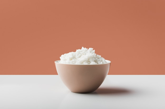 Arroz cozido branco cozido na tigela na mesa branca contra fundo marrom