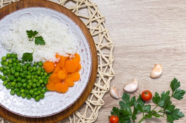 Arroz cozido com legumes e salsa no prato na mesa de madeira