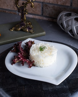 Arroz cozido com manjericão em cima da mesa
