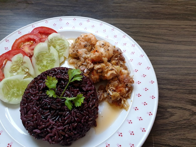 Arroz cozido e camarão frito com alho e pimenta com pepino e tomate.