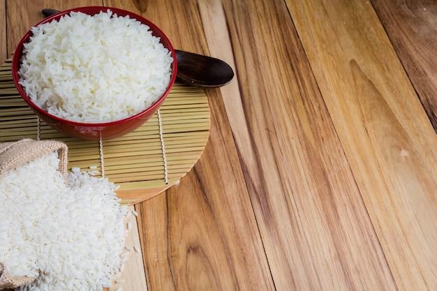 Arroz cozido em um copo vermelho colocado no chão de madeira compensada.