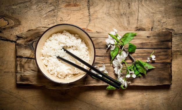 Arroz cozido em uma tigela e sakura. em uma mesa de madeira.