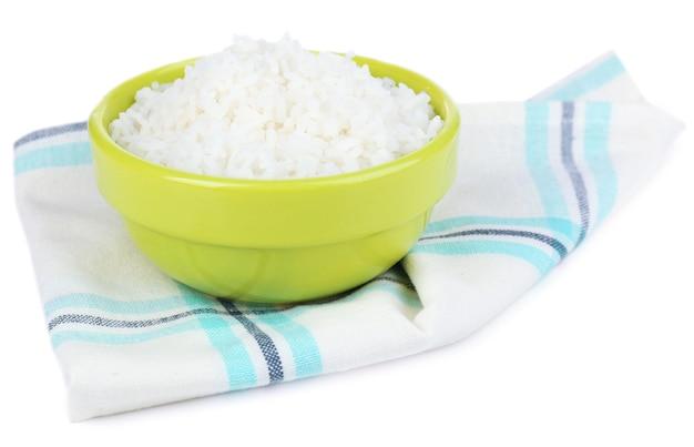 Arroz cozido em uma tigela no guardanapo isolado na superfície branca