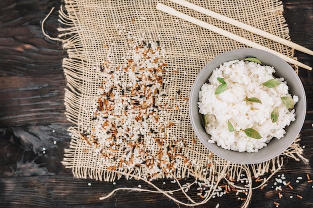 Arroz cozido perto de pauzinhos e grãos derramados