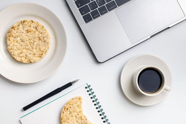 Arroz crocante com café perto do laptop e notebook.