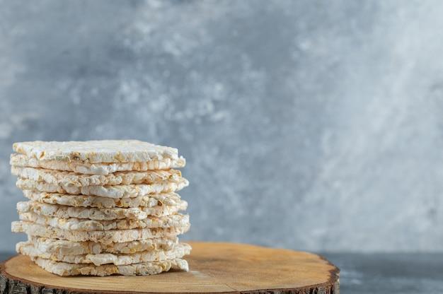 Arroz crocante de dieta seca em volta do pão isolado na peça de madeira.