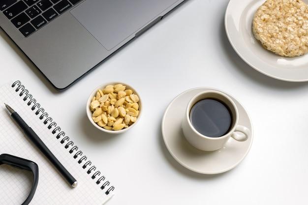 Arroz crocante rodadas com amendoim, xícara de café perto do laptop, fitness tracker e notebook.