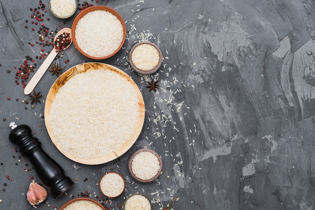 Arroz cru branco com especiarias secas; dente de alho e pimenta moinho em pano de fundo concreto