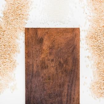 Arroz cru com tábua de cortar madeira