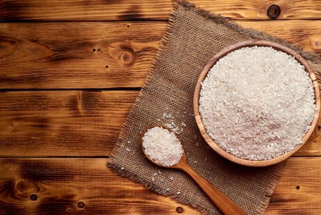 Arroz cru em uma tigela de madeira com a colher de pau cheia de arroz, fundo rústico.