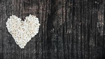 Arroz cru feito com coração no fundo texturizado de madeira preto