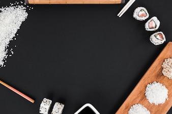 Arroz cru; pauzinhos; molho de sushi e soja em fundo preto