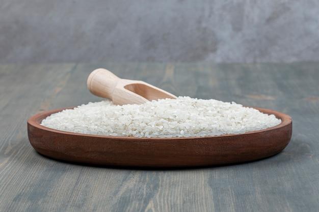 Arroz cru saudável com colher de pau em uma mesa de madeira