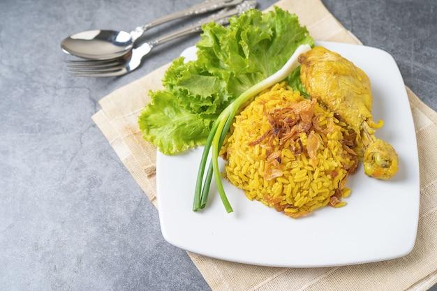 Arroz de biryani de comida muçulmana amarelo com frango em um prato branco no chão