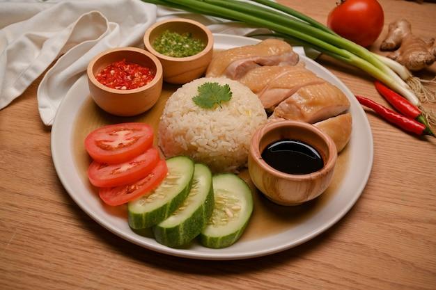 Arroz de frango hainanês com molho de pimenta e molho de soja doce e vegetais frescos em uma mesa de madeira