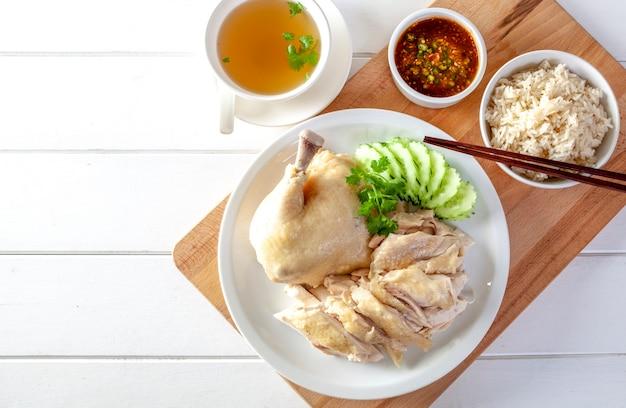 Arroz de frango hainanese, frango ao vapor com arroz, khao mun kai em fundo de madeira