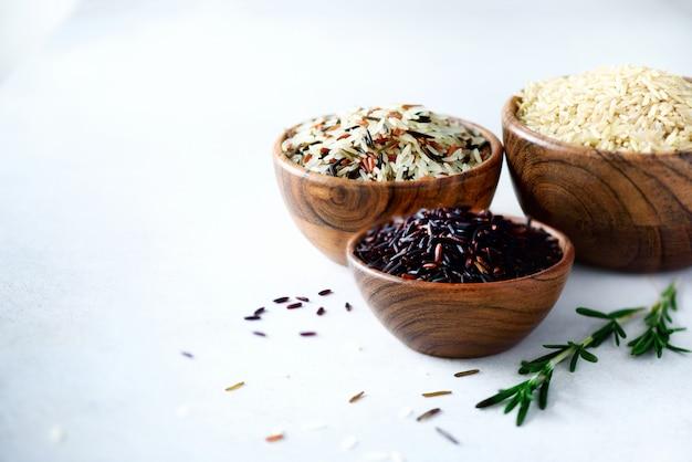 Arroz de jasmim, arroz marrom, preto e vermelho. variedade mista de grãos em bacias de madeira em concreto cinza, cópia espaço