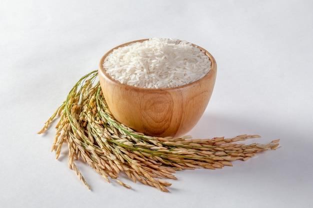 Arroz de jasmim tailandês em uma tigela de madeira e arroz isolado em um fundo branco