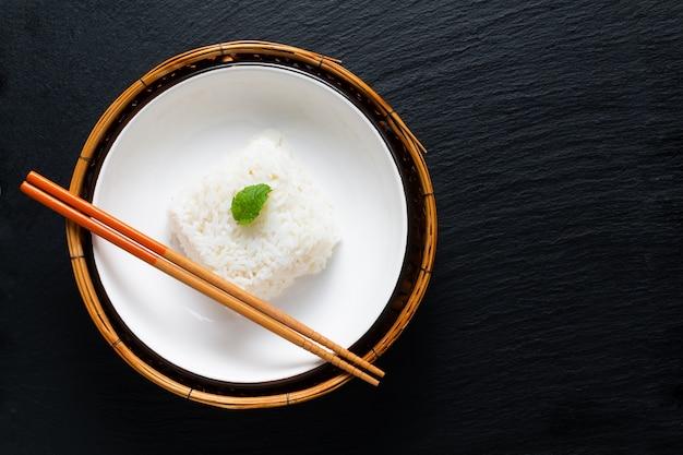 Arroz de jasmim thail em tigela de cerâmica e bandeja de bambu em ardósia preta boardç