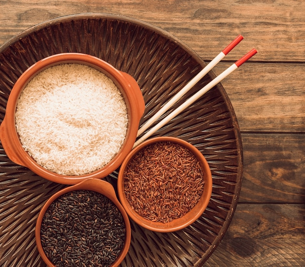 Arroz de jasmim vermelho; arroz preto e arroz branco na bandeja de madeira com pauzinhos