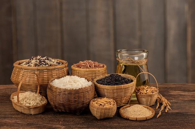 Arroz de jasmim vermelho, branco e marrom, sementes de frutas vermelhas e óleo em uma superfície de madeira velha.