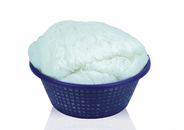 Arroz de macarrão em uma cesta isolada no branco
