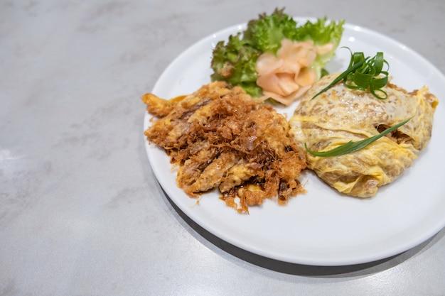 Arroz de omelete servido com carne de porco frita fatiada, comida japonesa em estilo tailandês