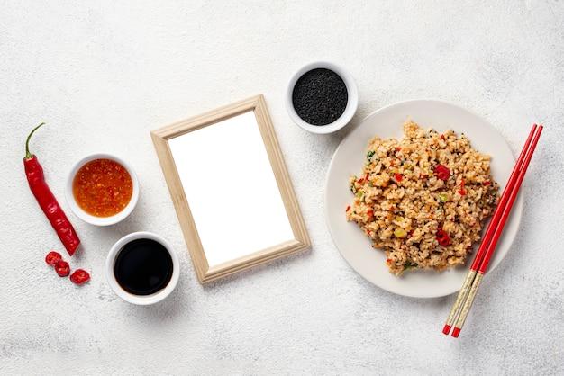 Arroz de vista superior com legumes em pauzinhos de prato e molho de soja com moldura em branco