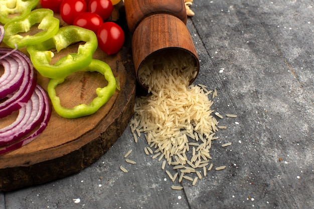 Arroz de vista superior, juntamente com cebola fatiada, pimentão verde e tomate no cinza