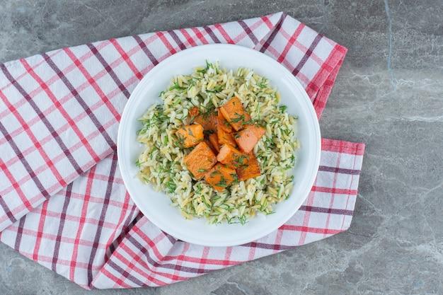 Arroz e cenouras fatiadas no prato, na toalha, na mesa de mármore.