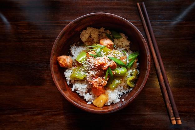 Arroz em molho com legumes salteados, abacaxi e salmão em uma tigela de madeira