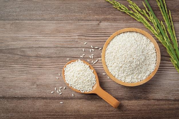 Arroz em tigela de madeira e colher de pau com planta de arroz