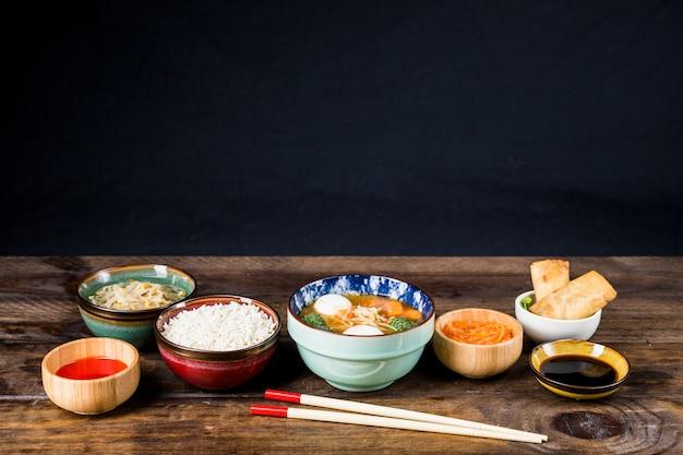 Arroz; feijão brotado; rolinho primavera; sopa de bola de peixe e molhos com pauzinhos na mesa contra fundo preto