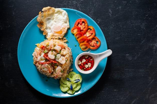 Arroz fritado com camarão e ovo frito na tabela de madeira preta, alimento tailandês.