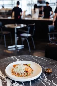 Arroz fritado do alho com os salmões grelhados no tampo da mesa de mármore preto com fundo do borrão.