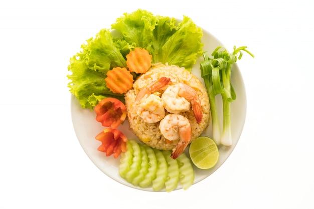 Arroz frito com camarão e camarão no topo em chapa branca