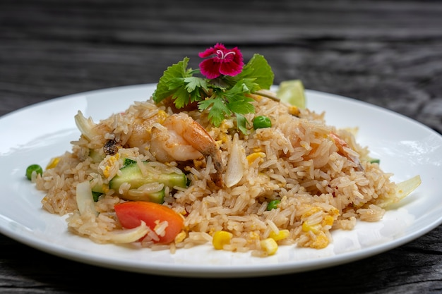 Arroz frito com camarão e legumes em um prato branco sobre uma velha mesa de madeira, close-up. comida tailandesa, culinária tailandesa. arroz frito com frutos do mar em restaurante