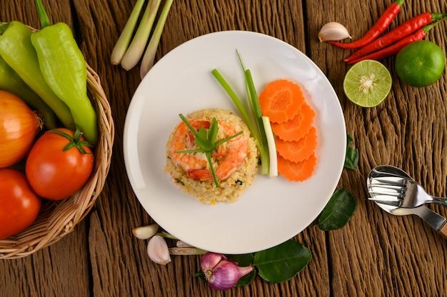 Arroz frito com camarão em um prato branco sobre uma mesa de madeira