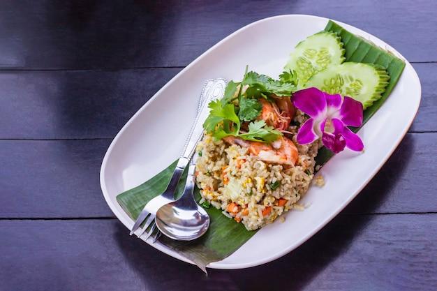 Arroz frito com camarão no prato de cerâmica branca decorado com orquídea colocar