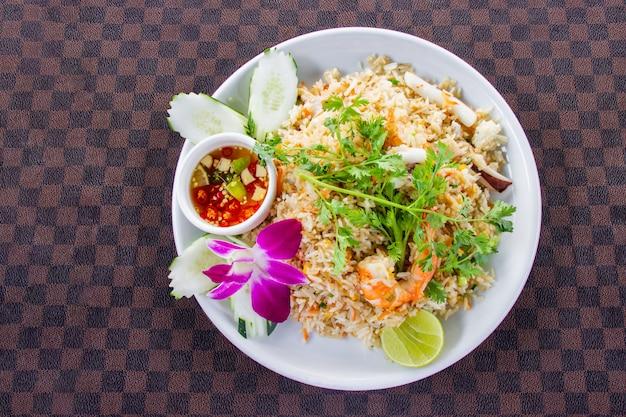 Arroz frito com camarão no prato de cerâmica branca decorado com orquídea