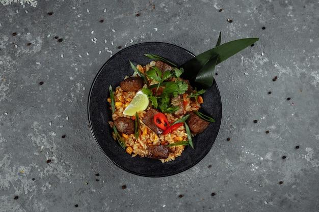 Arroz frito com carne e legumes em um cinza texturizado.