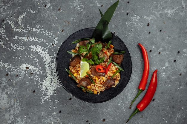 Arroz frito com carne e legumes em um plano de fundo texturizado cinza.