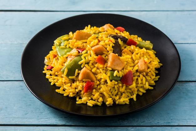 Arroz frito com frango e legumes em chapa preta na mesa de madeira azul.