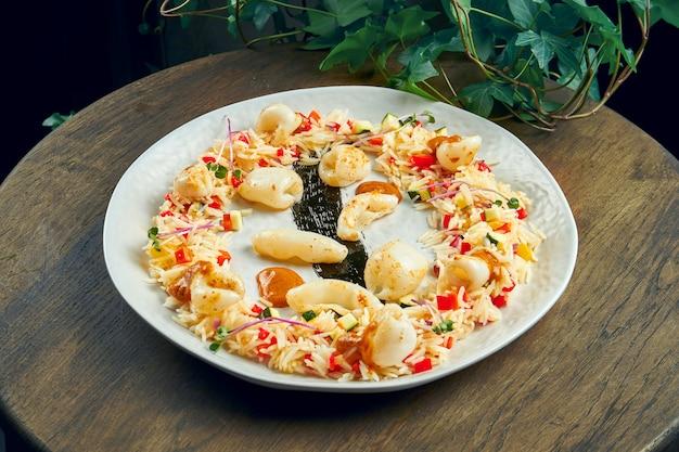 Arroz frito com lulas e legumes em um prato branco sobre uma superfície de madeira. foco seletivo