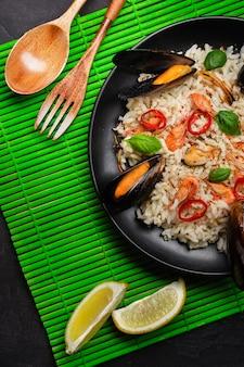 Arroz frito com marisco, mexilhões, camarões, manjericão em uma placa preta com uma colher de pau e um garfo na esteira de bambu verde e mesa de pedra. vista do topo.
