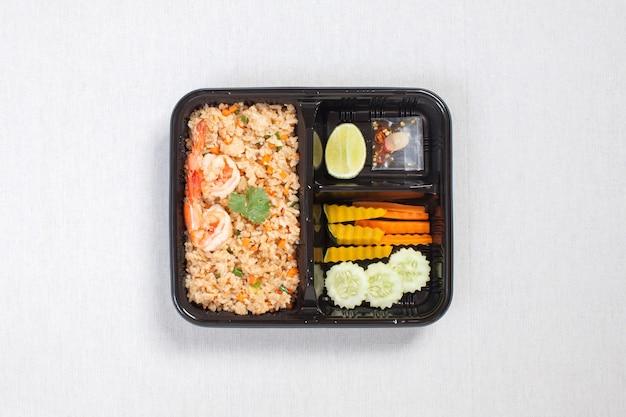 Arroz frito com óleo de camarão e camarão colocado em uma caixa de plástico preta, coloque sobre uma toalha de mesa branca, caixa de comida