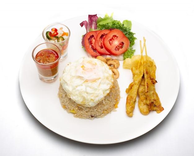 Arroz frito com ovo frito com carne de porco grelhada e salada