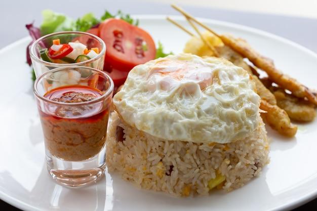 Arroz frito com ovo frito com porco assado e salada