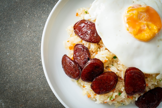 Arroz frito com ovo frito e linguiça chinesa - comida caseira em estilo asiático