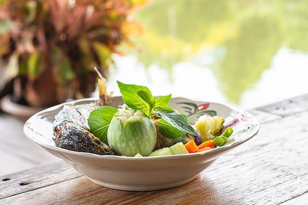 Arroz frito com pimenta picante com peixe e legumes em chapa branca
